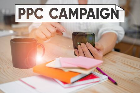 Handwriting text Ppc Campaign. Conceptual photo use PPC in order to promote their products and services woman using smartphone office supplies technological devices inside home