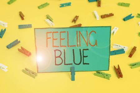 Text sign showing Feeling Blue. Business photo showcasing Feeling of desperation because of sadness or missing someone Colored clothespin papers empty reminder yellow floor background office