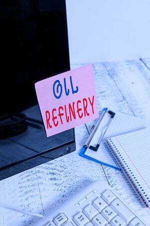 Writing note showing Oil Refinery. Business concept for industrial process of converting crude oil into petroleum Note paper taped to black computer screen near keyboard and stationary