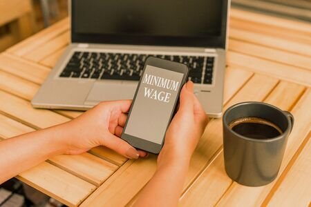 Writing note showing Minimum Wage. Business concept for the lowest wage permitted by law or by a special agreement woman with laptop smartphone and office supplies technology Фото со стока