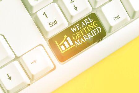 Escritura a mano conceptual mostrando que nos vamos a casar. Concepto Significado compromiso boda preparación pareja amorosa teclado de pc blanco con papel de nota sobre el fondo blanco. Foto de archivo