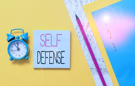Conceptual hand writing showing Self Defense. Concept meaning the act of defending one s is demonstrating when physically attacked Notepads marker colored paper sheets alarm clock wooden background