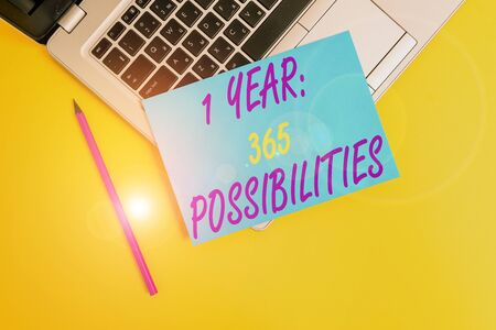 Conceptual hand writing showing 1 Year 365 Possibilities. Concept meaning Beginning of a New Day Lots of Chances to Start Metallic laptop small paper sheet pencil colored background