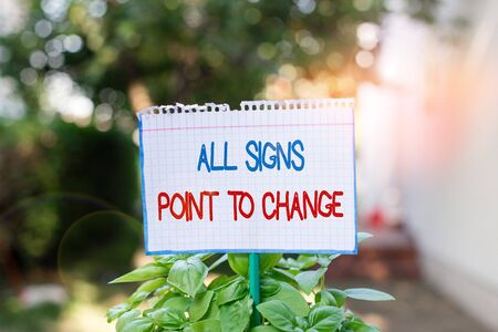 Word writing text All Signs Point To Change. Business photo showcasing Necessity of doing things differently new vision Plain empty paper attached to a stick and placed in the green leafy plants