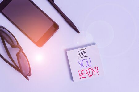 Handwriting text writing Are You Ready Question. Conceptual photo Setting oneself on the activity Being Prepared Eyeglasses colored sticky note smartphone cell pen cool pastel background Stock Photo