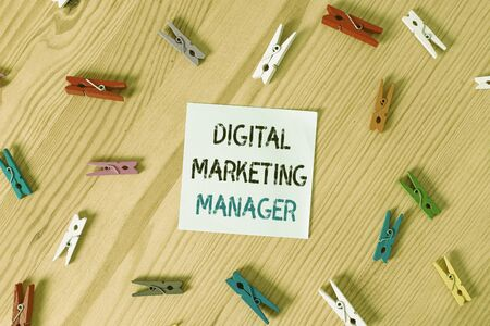 Writing note showing Digital Marketing Manager. Business concept for optimized for posting in online boards or careers Colored clothespin papers empty reminder wooden floor background office