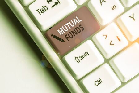 Handwriting text Mutual Funds. Conceptual photo collection of stocks bonds or other securities from investors White pc keyboard with empty note paper above white background key copy space Stock Photo