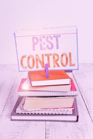 Text sign showing Pest Control. Business photo text analysisagement of a species that impacts adversely on huanalysis pile stacked books notebook pin clothespin colored reminder white wooden