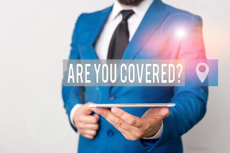 Writing note showing Are You Covered Question. Business concept for asking someone or patient if he have insurance Businessman in blue suite with a tie holds lap top in hands