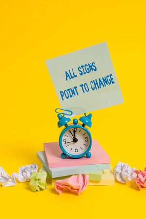 Text sign showing All Signs Point To Change. Business photo showcasing Necessity of doing things differently new vision Alarm clock sticky note paper balls stacked notepads colored background