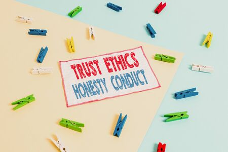 Conceptual hand writing showing Trust Ethics Honesty Conduct. Concept meaning connotes positive and virtuous attributes Colored clothespin paper reminder with yellow blue background