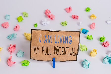 Text sign showing I Am Living My Full Potential. Business photo text Embracing opportunities using skills abilities Colored crumpled papers empty reminder white floor background clothespin
