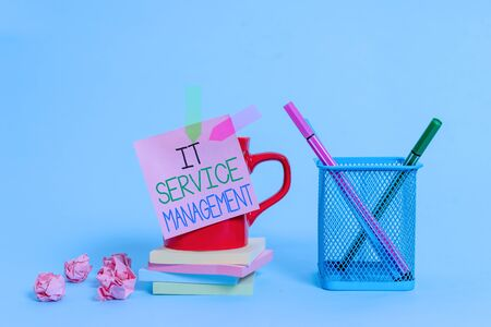 Word writing text It Service Management. Business photo showcasing Activity Directed by Policies Lifecycle of Technology Cup pens holder note banners stacked pads paper balls pastel background