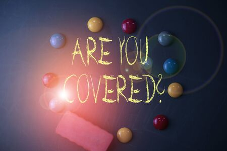 Word writing text Are You Covered Question. Business photo showcasing asking someone or patient if he have insurance Round Flat shape stones with one eraser stick to old chalk black board