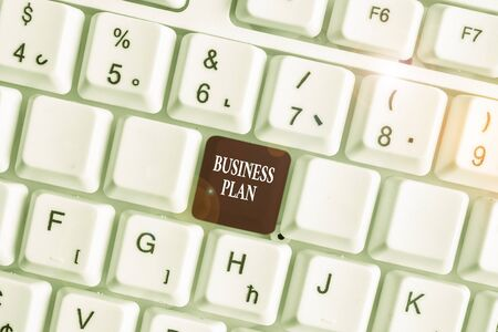 Text sign showing Business Plan. Business photo text Structural Strategy Goals and Objectives Financial Projections White pc keyboard with empty note paper above white background key copy space Banco de Imagens