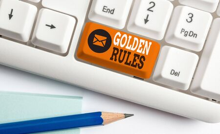 Conceptual hand writing showing Golden Rules. Concept meaning basic principle that should always follow to ensure success White pc keyboard with note paper above the white background