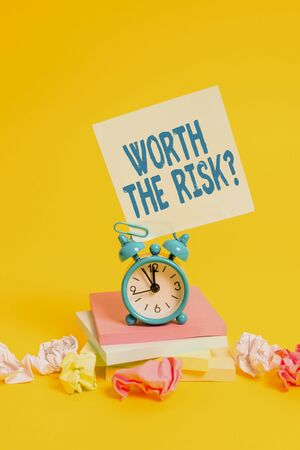 Text sign showing Worth The Risk Question. Business photo showcasing asking if certain action balanced with its reaction Alarm clock sticky note paper balls stacked notepads colored background