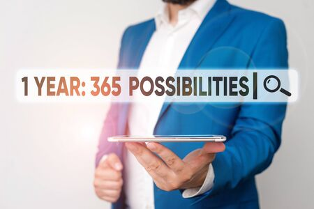 Text sign showing 1 Year 365 Possibilities. Business photo showcasing Beginning of a New Day Lots of Chances to Start Man in the blue suite and white shirt holds mobile phone in the hand
