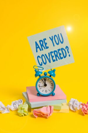 Text sign showing Are You Covered Question. Business photo showcasing asking someone or patient if he have insurance Alarm clock sticky note paper balls stacked notepads colored background