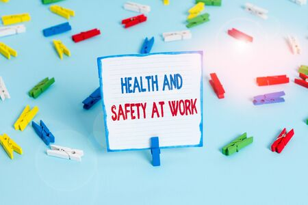 Conceptual hand writing showing Health And Safety At Work. Concept meaning Secure procedures prevent accidents avoid danger Colored clothespin papers empty reminder blue floor officepin