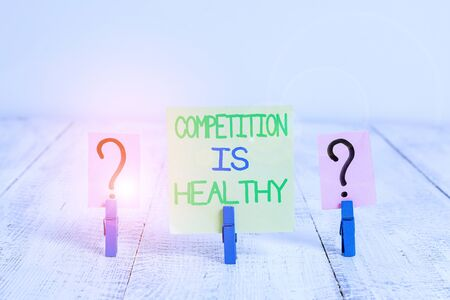 Conceptual hand writing showing Competition Is Healthy. Concept meaning Rivalry is good in any Venture leads to Improvement Crumbling sheet with paper clips placed on the wooden table
