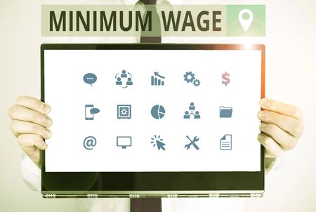 Word writing text Minimum Wage. Business photo showcasing the lowest wage permitted by law or by a special agreement Male human holding thick textured cardboard of business promotion concept