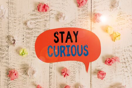 Conceptual hand writing showing Stay Curious. Concept meaning attention through being inexplicable or highly unusual Colored speech bubble paper balls wooden rustic vintage background 免版税图像