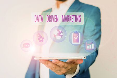 Conceptual hand writing showing Data Driven Marketing. Concept meaning Strategy built on Insights Analysis from interactions Male human wear formal suit presenting using smart device