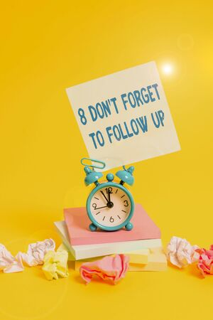 Text sign showing 8 Don T Forget To Follow Up. Business photo showcasing asking someone to keep connection with others Alarm clock sticky note paper balls stacked notepads colored background