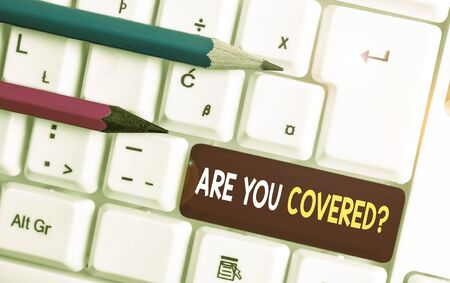 Conceptual hand writing showing Are You Covered Question. Concept meaning asking someone or patient if he have insurance White pc keyboard with note paper above the white background Stockfoto