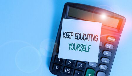 Text sign showing Keep Educating Yourself. Business photo showcasing dont stop studying Improve yourself using Courses Portable electronic calculator device blank sticky note colored background Stock Photo