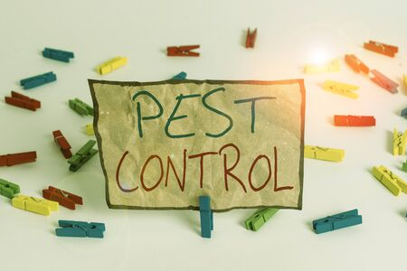 Word writing text Pest Control. Business photo showcasing analysisagement of a species that impacts adversely on huanalysis Colored clothespin papers empty reminder white floor background office