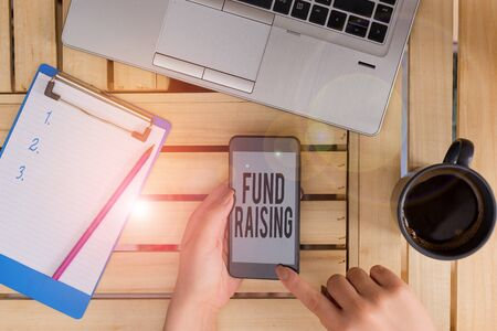 Conceptual hand writing showing Fund Raising. Concept meaning the act of seeking to generate financial support for a charity woman with laptop smartphone and office supplies technology Reklamní fotografie