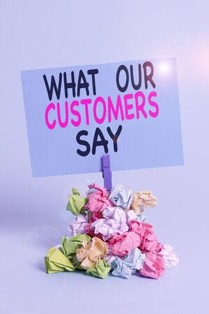 Text sign showing What Our Customers Say. Business photo text to know Users Feedback the Consumers Reactions Reminder pile colored crumpled paper clothespin reminder blue background