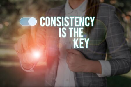 Text sign showing Consistency Is The Key. Business photo showcasing full Dedication to a Task a habit forming process Woman wear formal work suit presenting presentation using smart device Imagens