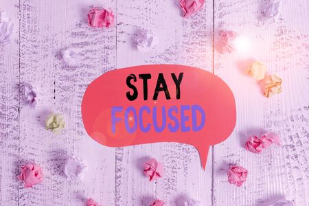 Conceptual hand writing showing Stay Focused. Concept meaning direct time and attention to a limited number of issues Colored speech bubble paper balls wooden rustic vintage background
