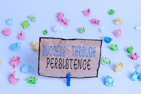 Text sign showing Success Through Persistence. Business photo text never give up in order to reach achieve dreams Colored crumpled papers empty reminder white floor background clothespin