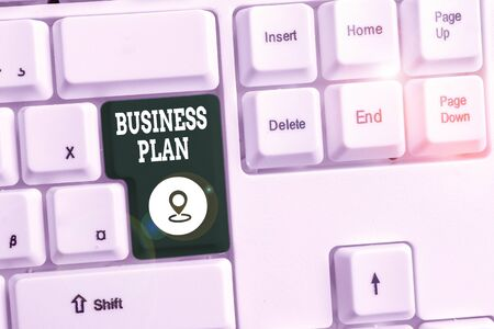 Conceptual hand writing showing Business Plan. Concept meaning Structural Strategy Goals and Objectives Financial Projections White pc keyboard with note paper above the white background Banco de Imagens