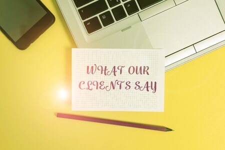 Text sign showing What Our Clients Say. Business photo text testimonials or feedback of aclient about the product Metallic laptop pencil squared paper sheet smartphone colored background Stockfoto