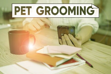Handwriting text Pet Grooming. Conceptual photo hygienic care and enhancing the appearance of the pets woman using smartphone office supplies technological devices inside home