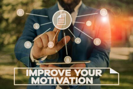 Handwriting text writing Improve Your Motivation. Conceptual photo Boost your self drive Enhance Motives and Goals Male human wear formal work suit presenting presentation using smart device Stock Photo