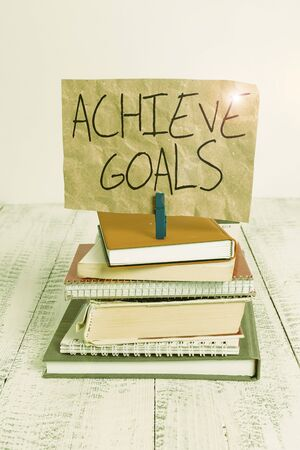 Writing note showing Achieve Goals. Business concept for Results oriented Reach Target Effective Planning Succeed pile stacked books notebook pin color reminder white wooden Reklamní fotografie