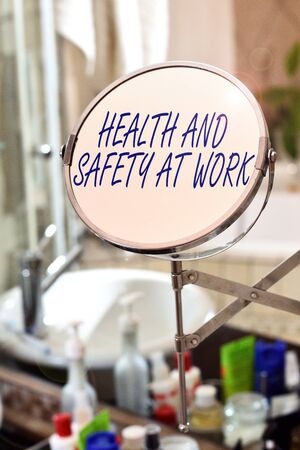 Handwriting text Health And Safety At Work. Conceptual photo Secure procedures prevent accidents avoid danger Round shape mirror and toiletries placed next to sink in a modern bathroom Foto de archivo - 131298306