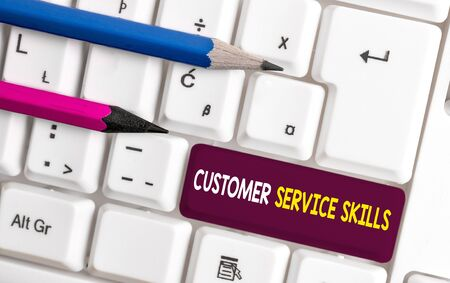 Conceptual hand writing showing Customer Service Skills. Concept meaning Aptitude to master to improve dealings with client White pc keyboard with note paper above the white background