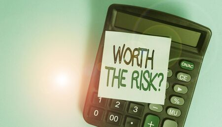 Text sign showing Worth The Risk Question. Business photo showcasing asking if certain action balanced with its reaction Portable electronic calculator device blank sticky note colored background