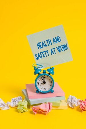 Text sign showing Health And Safety At Work. Business photo showcasing Secure procedures prevent accidents avoid danger Alarm clock sticky note paper balls stacked notepads colored background Foto de archivo - 131298385