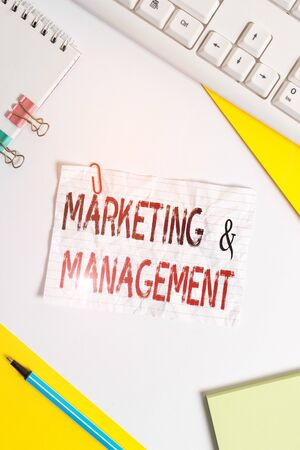 Word writing text Marketing And Management. Business photo showcasing process of developing strategies for product Flat lay above table with pc keyboard and copy space paper for text messages Banco de Imagens - 131298523