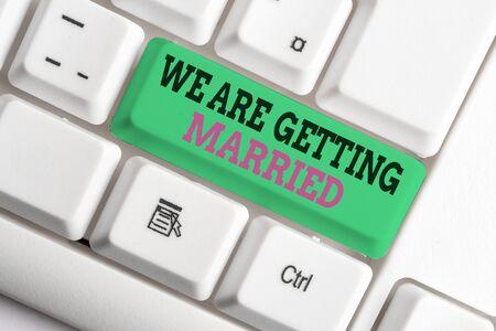 Escritura de texto escrito, nos vamos a casar. Foto conceptual preparación de la boda de compromiso pareja amorosa teclado de pc blanco con papel de nota vacío sobre fondo blanco espacio de copia clave