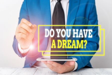 Conceptual hand writing showing Do You Have A Dream Question. Concept meaning asking someone about life goals Achievements Businessman pointing with pen in empty copy space Stock Photo