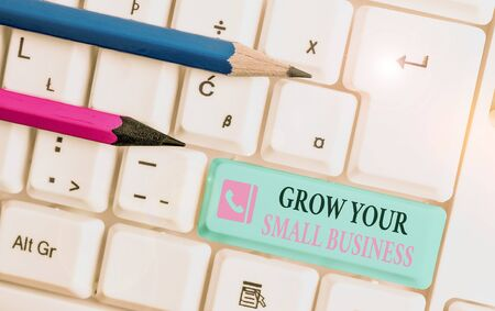 Word writing text Grow Your Small Business. Business photo showcasing company generates positive cash flow Earn White pc keyboard with empty note paper above white background key copy space Banco de Imagens